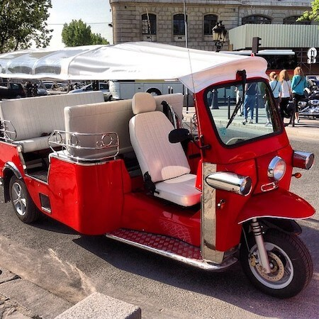 Photo of an electric Paris tuk tuk that's one of the best tours of Paris for families with kids. #tuktuk #parisbytuktuk #tuktuktour #paristour #tourofparis