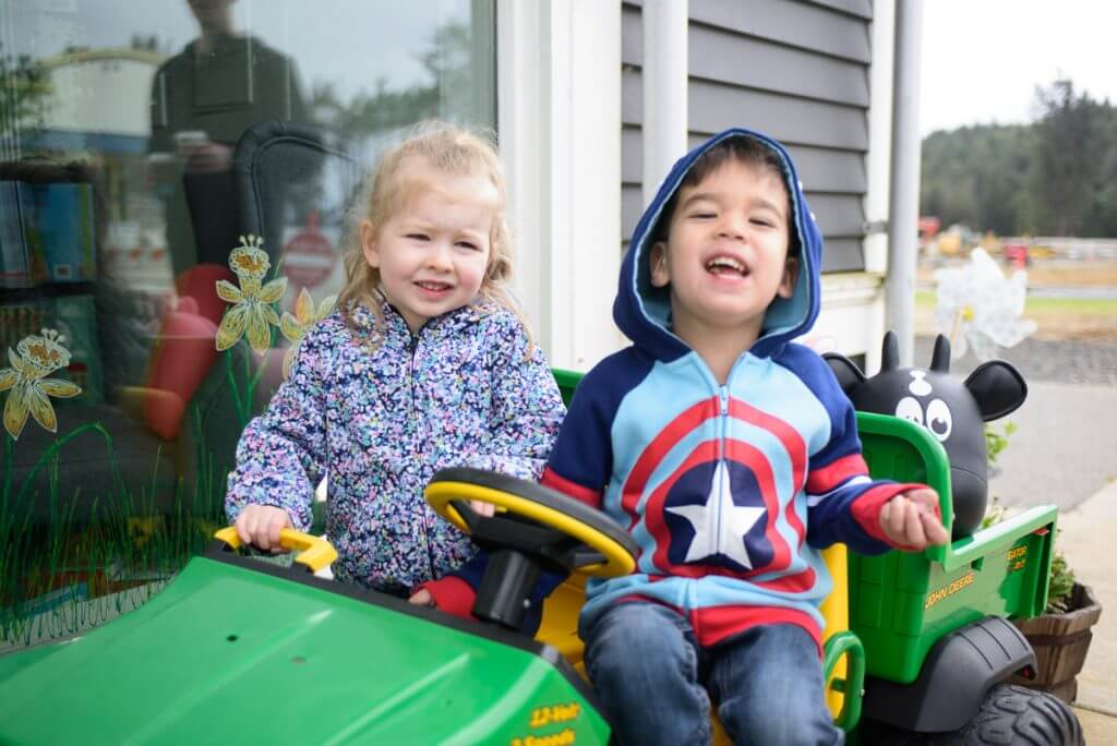 Photo of kids sitting in a John Deere toy tractor outside Seabrook Kids in Seabrook, Washington on the WA coast #seabrook #seabrookkids #seabrookwa #washingtonstate #washingtoncoast