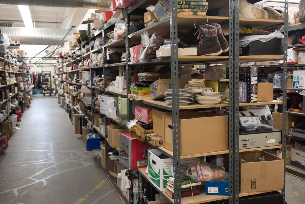 This warehouse is in a super secret location and is filled with treasures sold online. That means you can shop for Halloween costumes at Goodwill without leaving your house! Image of massive shelves stuffed with all kinds of thrift store items.