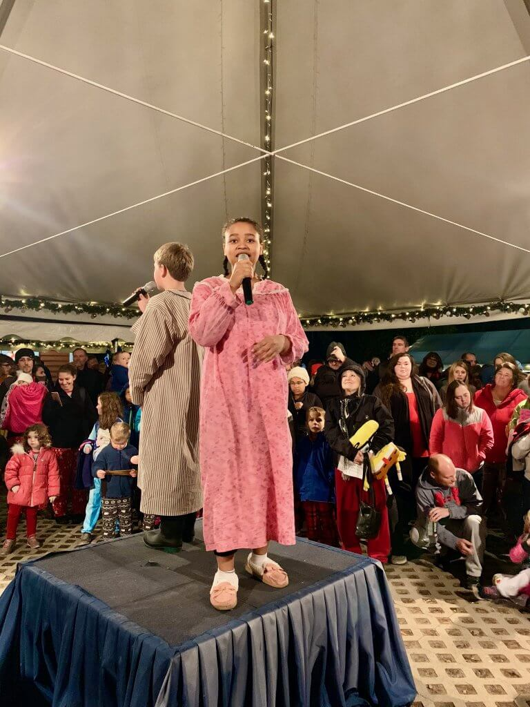 "All Aboard the Polar Express™ Train Ride at Mt Rainier Railroad and Logging Museum review featured by top Seattle blogger, Marcie in Mommyland: Photo of a girl dressed in a pink nightgown and a boy wearing a brown robe singing ""Believe"" in a Christmas-themed outdoor tent"