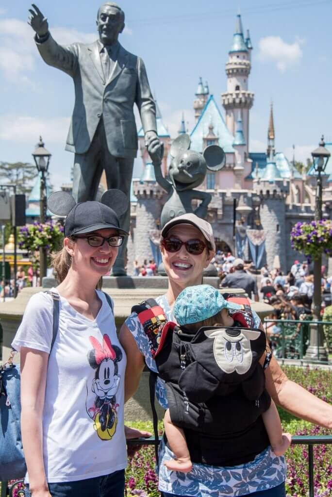 Grandma, Mom and Baby in a Tula carrier in front of the castle at Disneyland