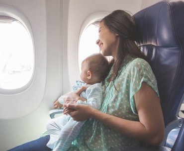 Find out my top tips for flying with a baby on an airplane. Image of a woman holding an infant on an airplane