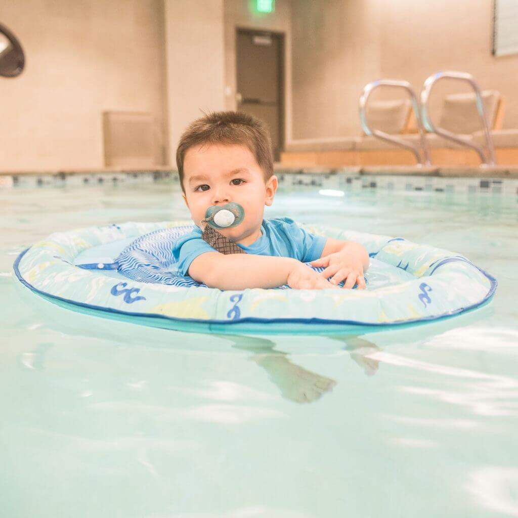 Photo of a baby swimming in a hotel pool in a Swimways pool float #swimways #babyswimming #binky #staycation #summertravel