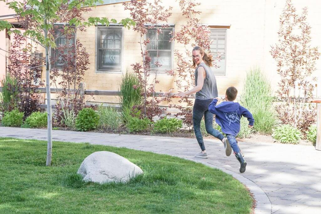 Photo of a mom and boy chasing each other in a park in Withrop, Washington #playingtag #playingchase #familyexercise #active #exercise