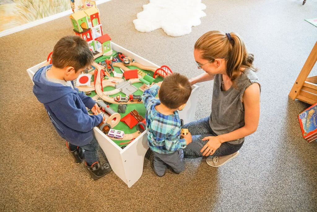 Photo of kids playing at a train table, which is a fun thing to do in Withrop with kids. #winthrop #winthropwa #pnw #bookstore #traintable