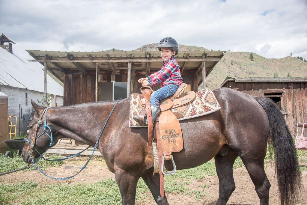 Photo of a kid learning to ride a horse in Twisp, WA near Winthrop in the Methow Valley #winthrop #twisp #methowvalley #horses #horsebackriding