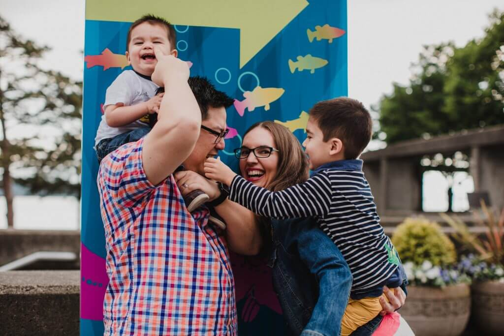 Silly family photo in front of the Seattle Aquarium sign at the Seattle waterfront, a top Seattle attraction for families #seattleaquarium #seattle #seattleattractions #seattlewaterfront