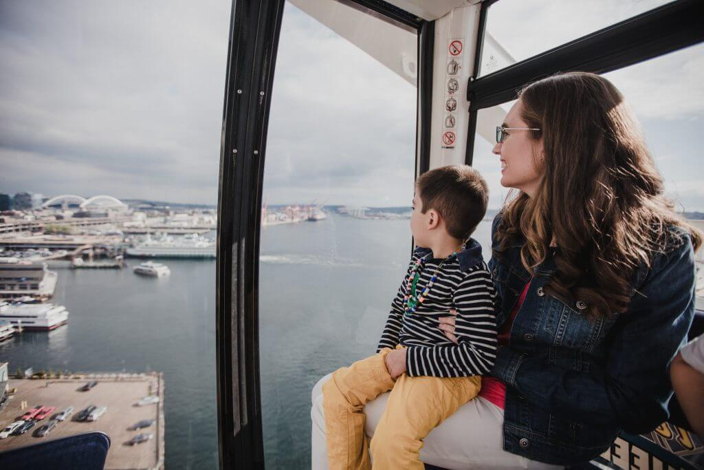 Photo of a Mom and son riding the Seattle Great Wheel, a top Seattle attraction on the Seattle Waterfront and a fun thing to do in Seattle with kids #seattlegreatwheel #seattle #seattlewa #pnw #pier57 #minerslanding #visitseattle #seattlewaterfront #seattletourism