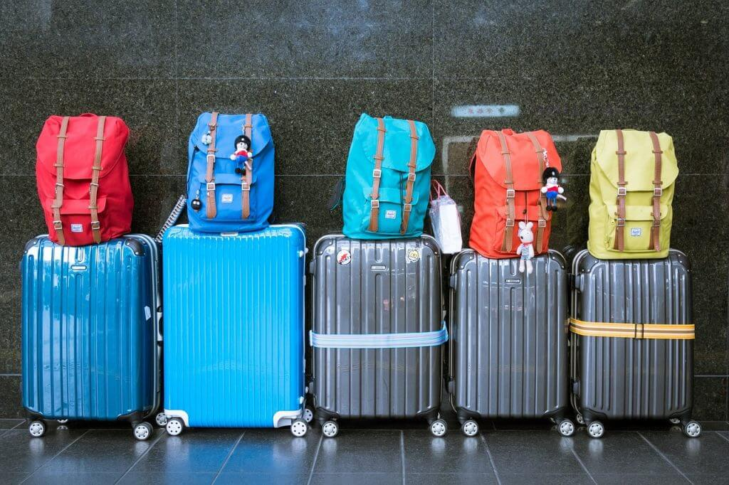 Investing in travel insurance for Hawaii can cover lost or damage bags. Photo of luggage for summer family travel with kids.