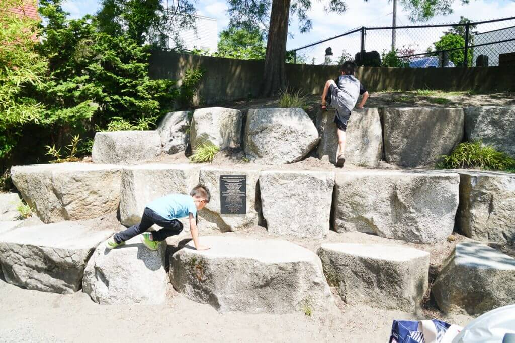 Photo of kids climbing on rocks at Donnie Chin Park in Seattle's International District (Seattle Chinatown) #chinatown #seattlewa #seattleinternationaldistrict #visitseattle #seattlepark #playground