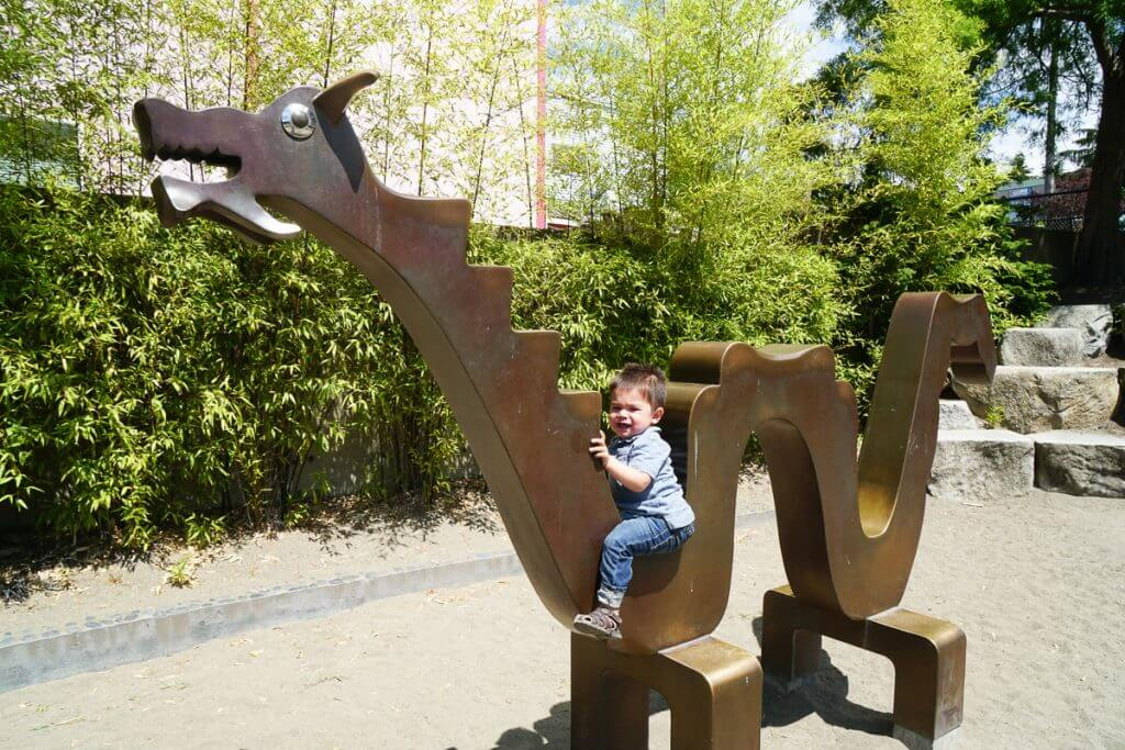 Photo of a toddler sitting in a dragon sculpture at a park in Seattle's Chinatown #seattlepark #dragonstatue #dragonsculpture #chinesepark #chinatownpark