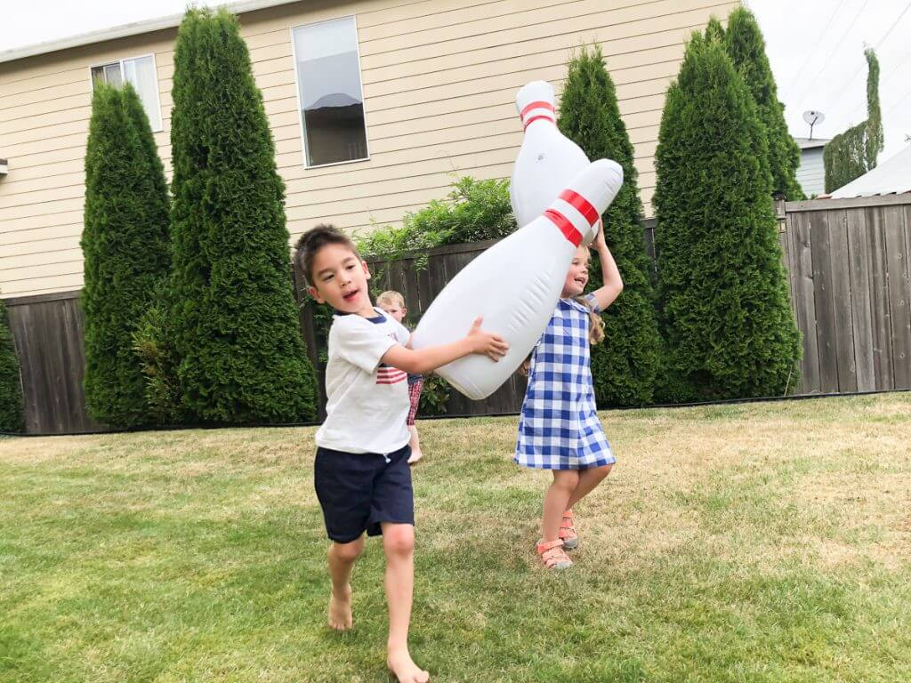 Photo of kids playing with inflatable bowling pins from Zulily #zulily #bowling #bbq #lawngames