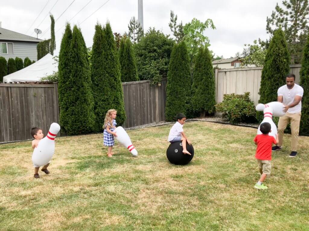 Photo of kids playing with inflatable bowling set from Zulily at a 4th of July BBQ #zulily #bowlingpins #lawngames #inflatable