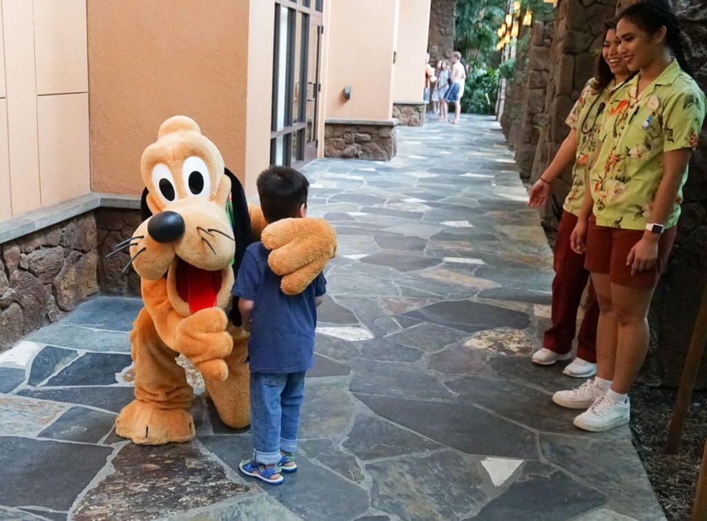 Photo of a boy meeting Pluto at Aulani, a Disney Resort & Spa on Oahu as part of a Disney pixie dust moment! #disneysmmc #disney #disneyaulani #aulani #aulaniresort #pluto