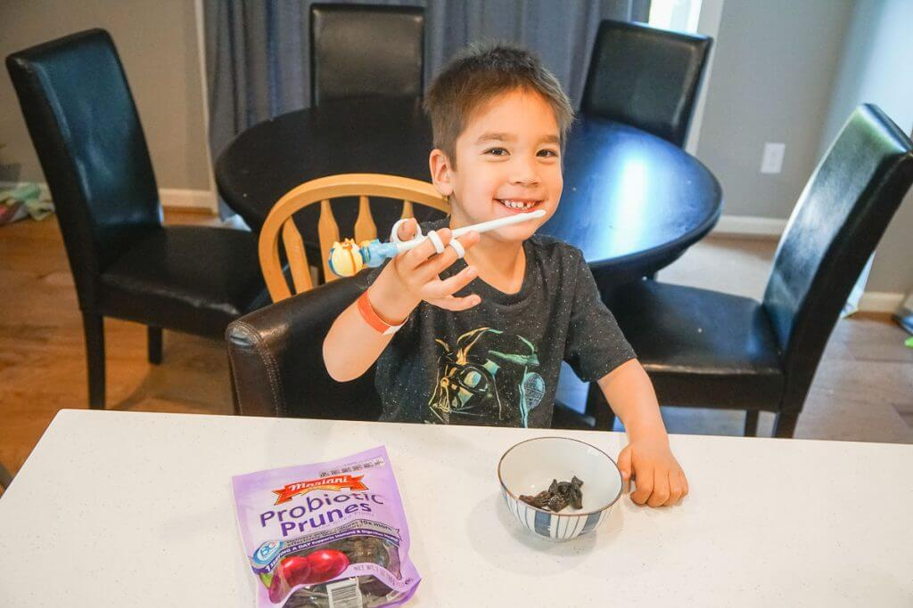 Photo of a boy eating dried prunes as his daily probiotic, which is good for digestion and healthy gut #marianipittedprunes #probiotic #healthyeats #healthysnack #driedfruit #prunes