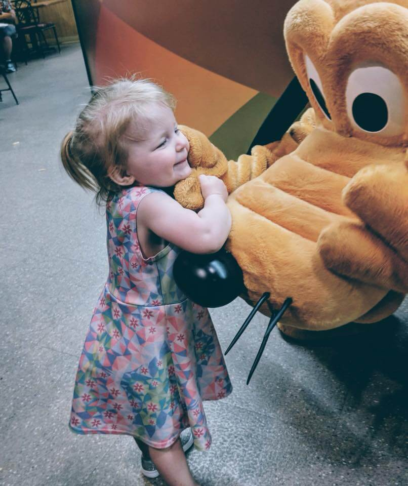 Photo of a girl making magical memories with Pluto at Walt Disney World with some Disney Pixie Dust magic #disney #disneysmmc #pluto #waltdisneyworld #disneypixiedust #pixiedust