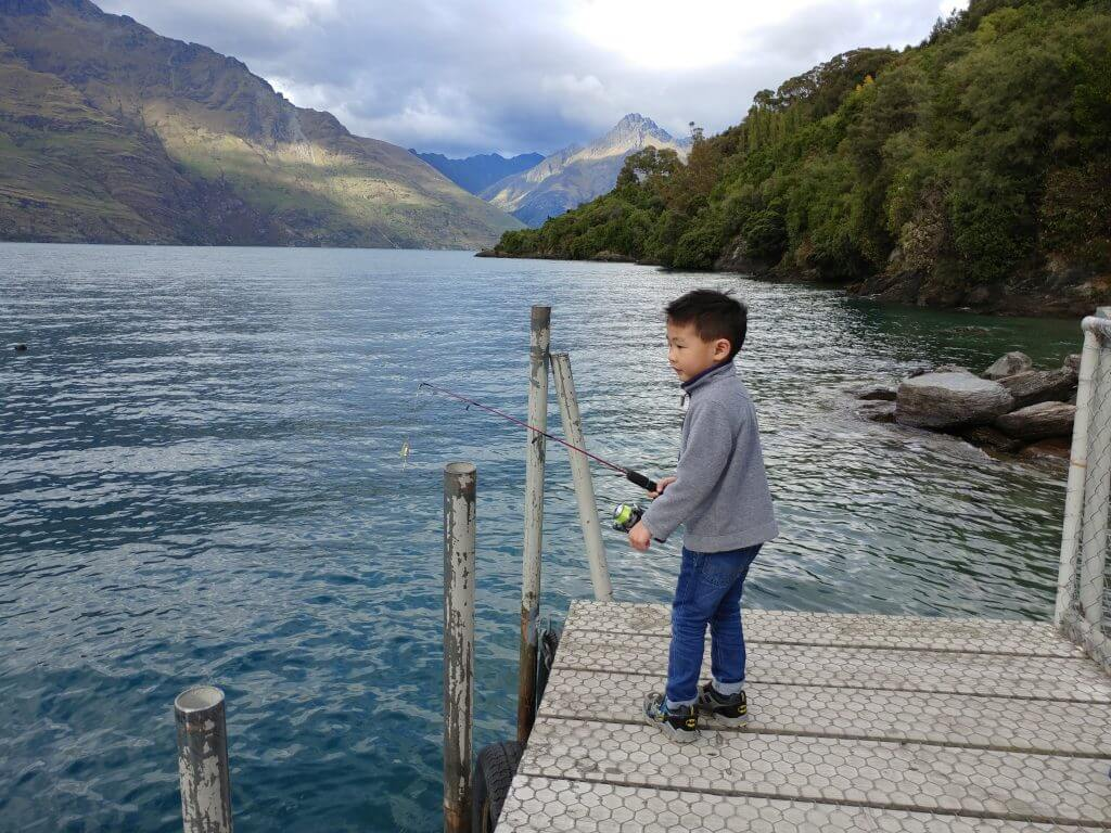 Photo of a boy fishing in New Zealand, a fun thing to do in New Zealand with kids #newzealand #fishing #queenstown #nz #familytravel