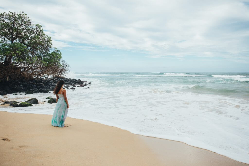 Photo of a woman watching the surf in Maui, a popular babymoon destination in Hawaii #maui #hawaii #babymoon #tropicalbabymoon #zikafreebabymoon