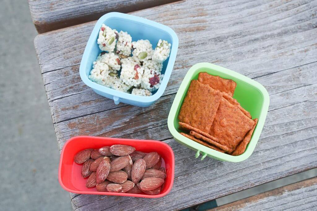 Photo of almonds, crackers, and other snacks perfect for a summer play date in the park or a toddler lunch or mom lunch idea #lunch #almonds #toddlerlunch #momlunch #momonthego