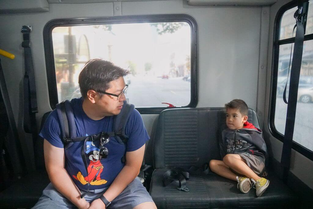 Photo of a Dad and son riding the new Seattle Waterfront Shuttle, a free thing to do in Seattle, WA #seattle #seattlewa #pnw #seattletourism #downtownseattle #seattlewithkids #familytravel