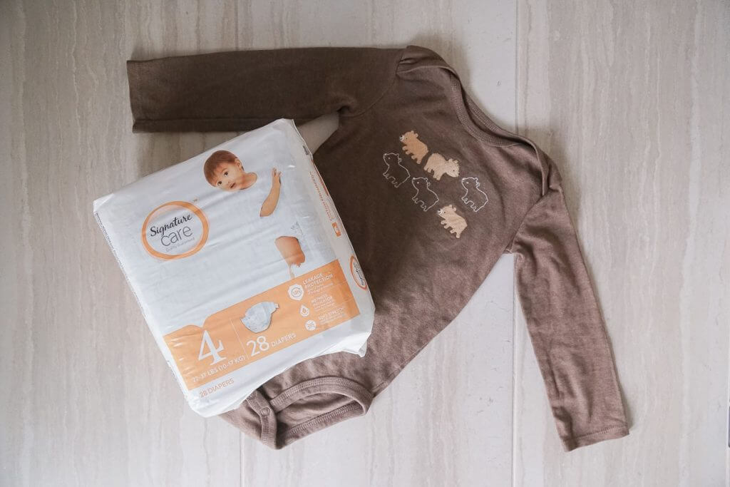 Photo of a baby onesie and a pack of Signature Care diapers, available at Albertsons and Safeway stores #diapers #onesie #travelwithababy #flyingwithababy #flyingtips #familytravel #travelwithkids