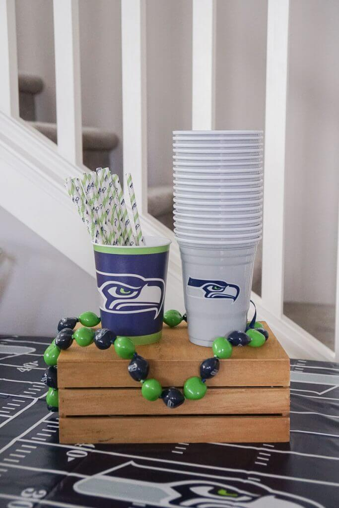 Photo of officially licensed NFL cups and kukui nut necklace for the Seattle Seahawks #seahawks #nfl #seattleseahawks #kukuinut #paperstraws #seahawksparty