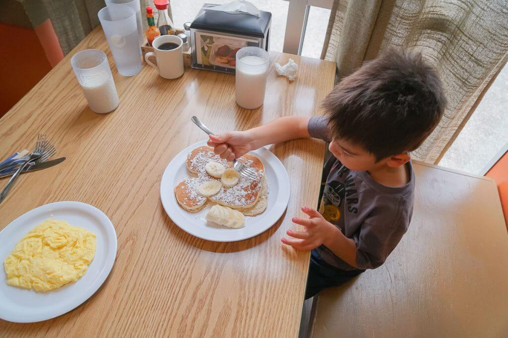 Photo of a boy eating a Mickey Mouse pancake at Saimin Says in Kent, WA #visitkentwa #saiminsays #mickeymousepancake