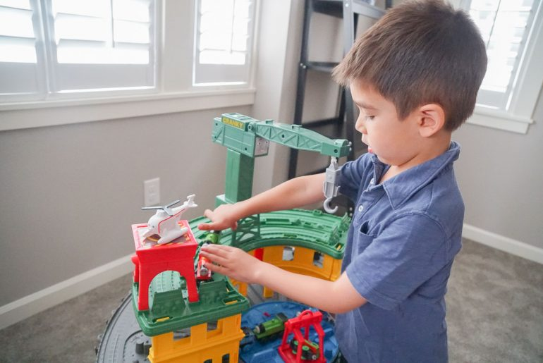 Photo of a boy playing with the Thomas Super Station, available at Walmart, which is a top holiday gift for 4 year olds #thomassuperstation #thomasandfriends #giftidea #preschooler