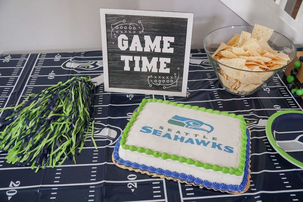 Photo of a Seattle Seahawks party table with an officially licensed NFL cake from DecoPac #decopac #seattleseahawks #nfl #nflcake #seahawks