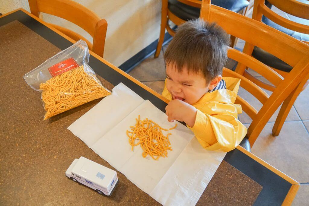 Photo of a toddler eating Indian snacks at Punjab Sweets in Kent, WA #visitkentwa #punjabsweets #indianfood #indiansnacks