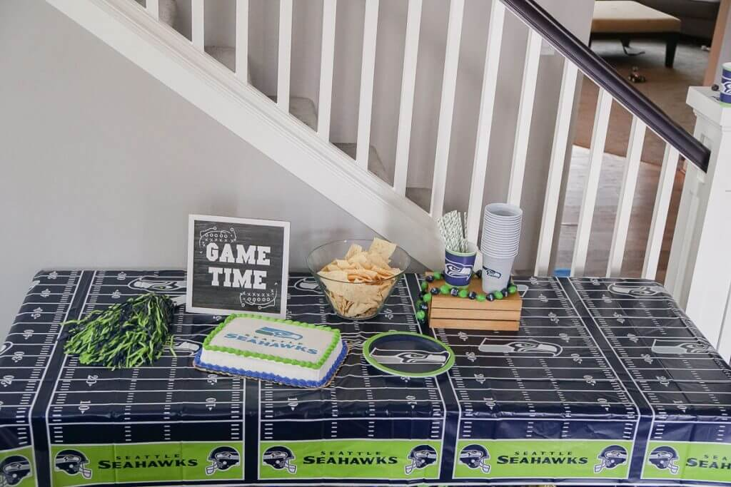 Photo of a Seattle Seahawks snack table featuring an officially licensed NFL cake from DecoPac #decopac #nfl #nflcake #footballcake #footballparty #footballtheme