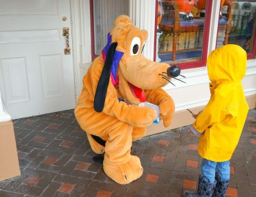 Photo of a boy meeting Pluto at Disneyland in the rain #disneyland #pluto #DLR