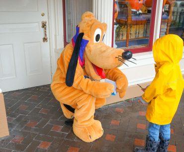 Photo of a boy meeting Pluto at Disneyland in the rain #disneyland #pluto #DLR