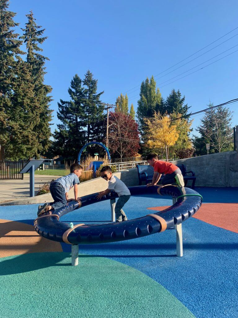Photo of kids playing with a spinning ring at Meadow Crest inclusive playground near Seattle, WA #inclusiveplayground #playground #preschoolers