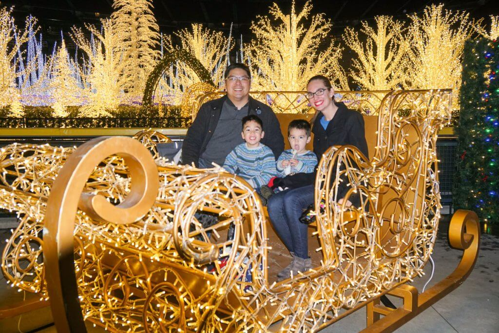 Photo of a family in Santa's Sleigh at Enchant Christmas in Seattle #enchantseattle #enchantchristmas #santa #sleigh