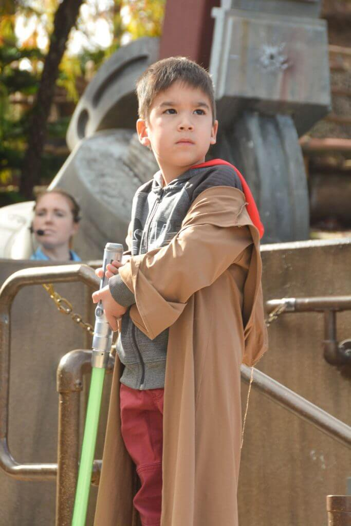 A young boy wears his Jedi robe holding a lightsaber during the Jedi Training: Trials of the Temple Star Wars experience at Walt Disney World in Florida. #jedi #lightsaber #disneyworld #waltdisneyworld