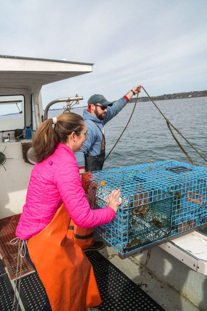 Guests can help push lobster traps into the water on this Portland Maine cruise in Casco Bay.