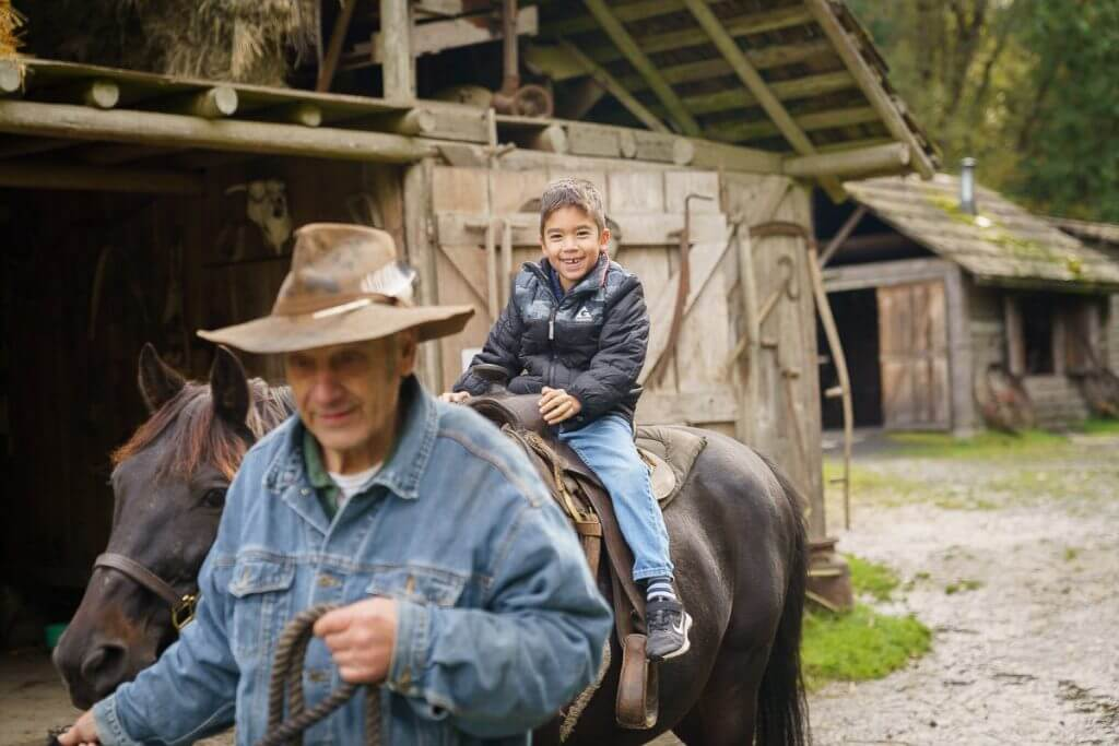 Pioneer Farm has lots of hands on experiences like horseback riding, blacksmithing, milking cows, feeding chickens and more.