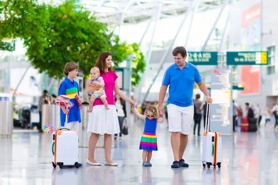 8 Tips for Getting Through Airport Security with Children featured by top US travel blogger, Marcie in Mommyland: Family traveling with kids. Parents with children at international airport with luggage. Mother and father hold baby, toddler girl and boy flying by airplane. Travel with child for summer vacation.