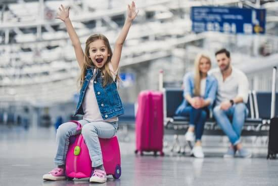 8 Tips for Getting Through Airport Security with Children featured by top US travel blogger, Marcie in Mommyland: Family in airport. Attractive young woman, handsome man and their cute little daughter are ready for traveling!