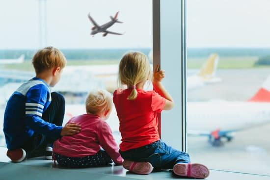 8 Tips for Getting Through Airport Security with Children featured by top US travel blogger, Marcie in Mommyland: kids wait looking at planes in airport, family travel concept
