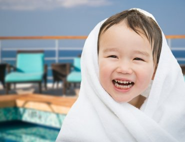 Best Cruises for Toddlers this Year featured by top US family travel blogger, Marcie in Mommyland: Happy Cute Mixed Race Chinese and Caucasian Boy On Cruise Ship Wrapped In A Towel.