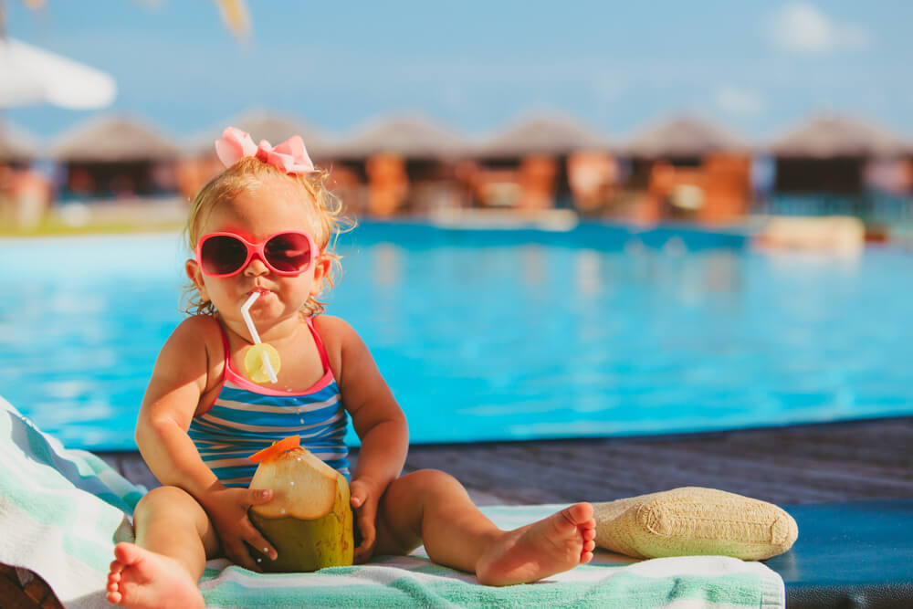 Best Cruises for Toddlers this Year featured by top US family travel blogger, Marcie in Mommyland: Photo of a toddler girl sipping a coconut drink on the beach