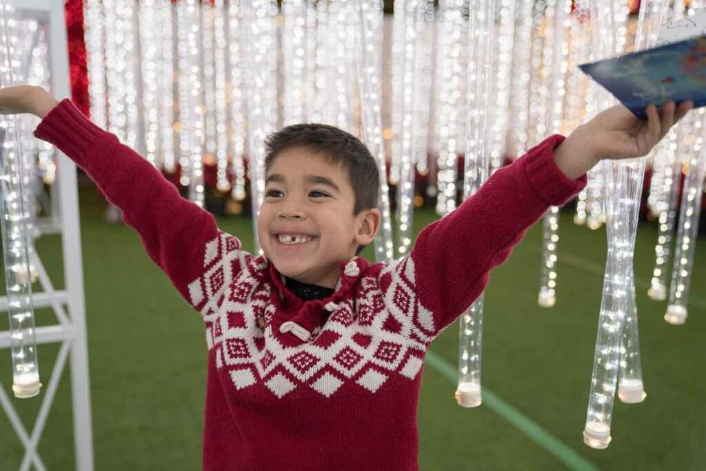 Lumaze Indoor Light Festival in Seattle review featured by top Seattle blogger, Marcie in Mommyland: A boy wearing a Christmas sweater looks elated as he stands in a room with hanging lights at Lumaze Seattle
