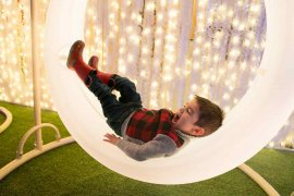 Lumaze Indoor Light Festival in Seattle review featured by top Seattle blogger, Marcie in Mommyland: A boy lays down in a circular lighted swing at Lumaze Seattle