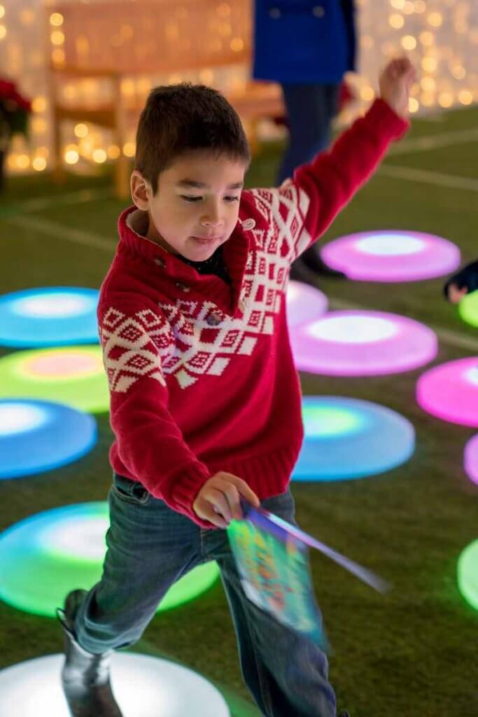 Lumaze Indoor Light Festival in Seattle review featured by top Seattle blogger, Marcie in Mommyland: A boy wearing a red Christmas sweater playing hopscotch on lighted discs at Lumaze Seattle