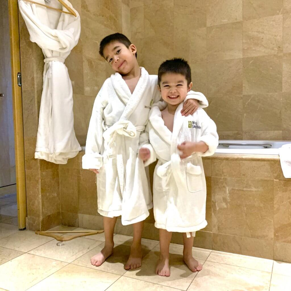 Christmas in Victoria BC: the Best Kid Friendly Festivities featured by top US family travel blogger, Marcie in Mommyland: Two boys wearing little white hotel bathrobes standing in the bathroom at the Inn at Laurel Point in Victoria, BC