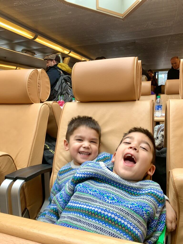 Christmas in Victoria BC: the Best Kid Friendly Festivities featured by top US family travel blogger, Marcie in Mommyland: Two boys in matching Christmas sweaters sit on the Clipper Ferry boat