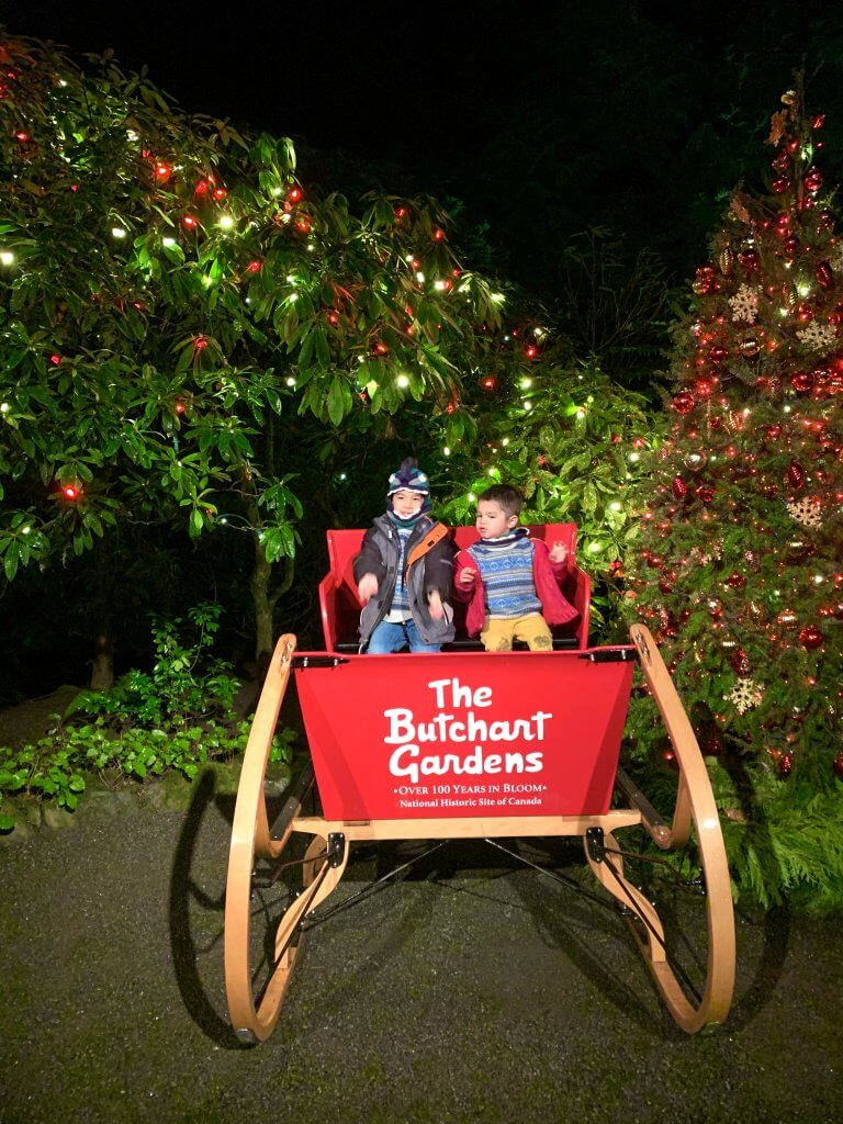 Christmas in Victoria BC: the Best Kid Friendly Festivities featured by top US family travel blogger, Marcie in Mommyland: Kids posing in Santa's Sleigh at the Magic of Christmas event at The Butchart Gardens in Victoria BC