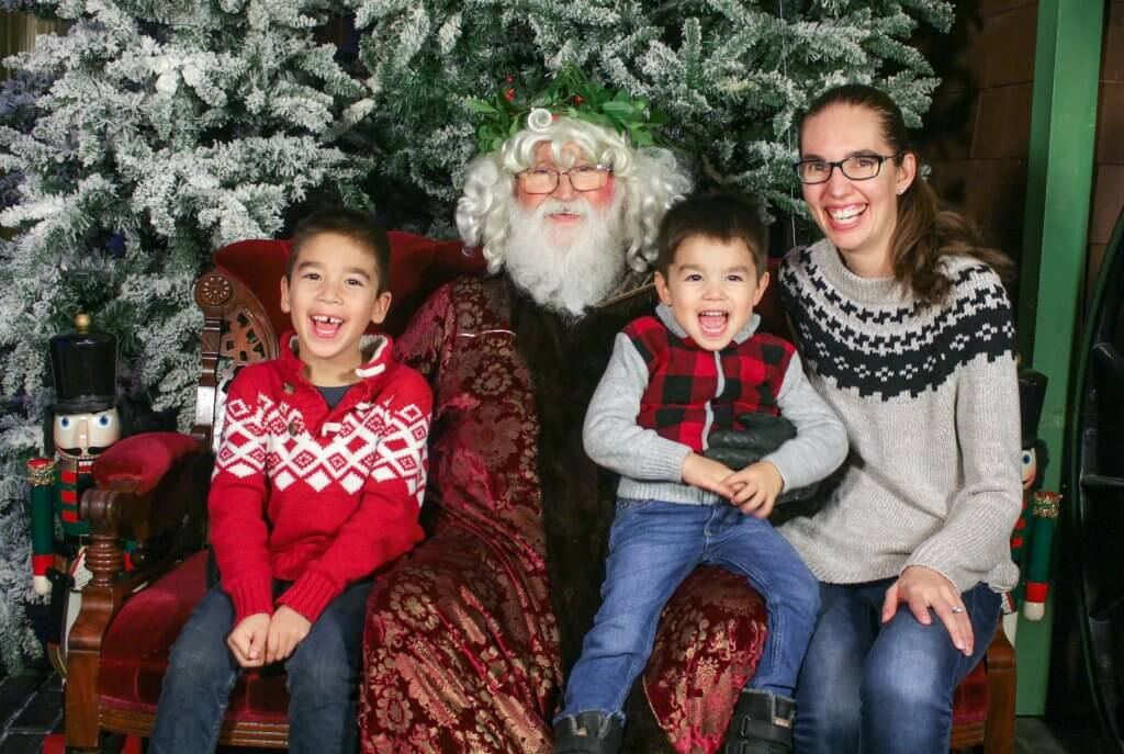 Christmas in Victoria BC: the Best Kid Friendly Festivities featured by top US family travel blogger, Marcie in Mommyland: A mom and two boys in Christmas sweaters post with Father Christmas in a Victorian Christmas photo
